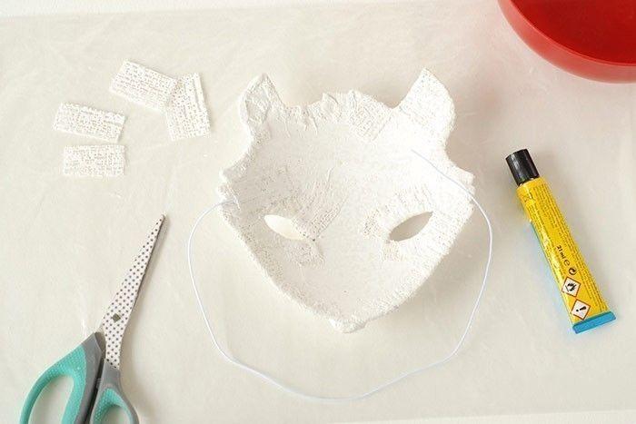 ETAPE 6/8 Prendre un élastique. Déposer un trait de colle foerte de part et d'autre du masque. Poser les extrémités dans la colle. Laisser sécher. Recouvrir de 2 morceaux de bandes plâtrées. Laisser sécher.