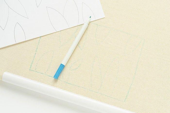 ETAPE 3/12 Mesurez le tour de votre bocal ou bouteille en verre, ajoutez environ 2cm sur votre dessin. Mesurez la hauteur sans modifier sur le dessin. Dessinez votre motif en suivant la trame de la toile. Cela permettra au motif d'être bien droit. Astuce : 2 cache-pots au punch needle peuvent être réalisés sur le grand tambour carré. Inspirez-vous du gabarit pour reproduire vos motifs à vos dimensions.