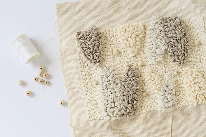ETAPE 9/12 A l'aide d'un fil et d'une aiguille, brodez des perles en bois de manière aléatoire : passez le fil sur l'envers de la toile, passez la perle dans l'aiguille et repiquez dans la toile, etc…