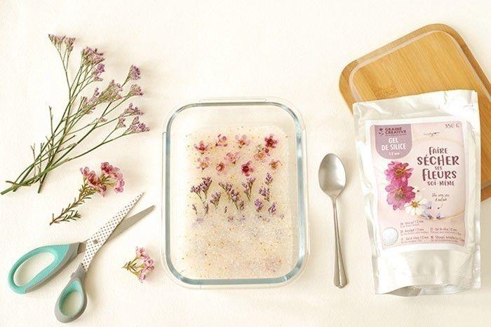 ETAPE 1/9 Faire sécher des fleurs avec le gel de silice Tapisser le fond d'une boîte hermétique de cristaux de gel de silice. Poser les fleurs coupées sans la tige. Recouvrir délicatement de cristaux à l'aide d'une petite cuillère. Fermer la boîte et laisser sécher 24 heures maximum.
