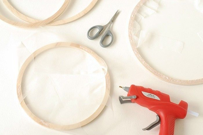 ETAPE 6/9 Anneaux avec des cercles en bois simples : Prendre 2 anneaux en bois simples de même dimension et en poser un sur le tulle. Rabattre les bords vers le centre et fixer le tulle au pistolet à colle sur le rebord en bois, le tendre pour éviter les plis. Maintenir le temps que la colle refroidisse. Couper le tulle qui dépasse au centre de l'anneau. Pour la finition, retourner l'anneau et coller par-dessus un anneau de même taille.