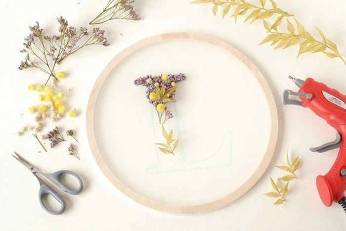 ETAPE 8/9 Coller les fleurs au pistolet à colle en suivant les contours de la lettre. S'aider si besoin d'une pince à épiler. Serrer les fleurs pour donner une densité. Retourner le tambour et enduire de colle pour solidifier l'ensemble. Pour la finition, retourner l'anneau et coller par-dessus un anneau de même taille.