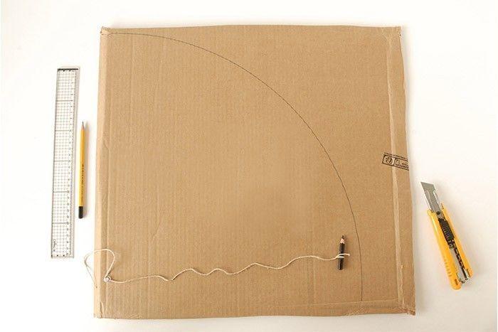 ETAPE 1/17 Le tapis de jeu en carton « Nature » Récupérer des grands cartons. Pour créer un tapis rond, prendre une ficelle, une pointe et un crayon. Nouez la ficelle à la pointe. Mesurer 40 cm et attacher le crayon à papier. Piquer la pointe à un angle du carton et tracer ¼ de cercle. Découper au cutter sur une plaque de coupe (manipulation par un adulte). Préparer de cette façon 4 quarts de cercle. 