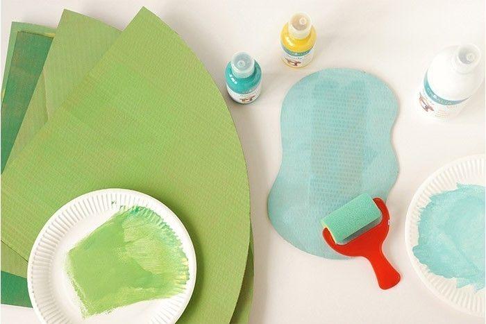 ETAPE 2/17 Tracer la silhouette d'un lac sur un carton. Découper au cutter (manipulation par un adulte). Peindre les cartons avec le rouleau en mousse dans des nuances de verts différents, l'occasion d'apprendre à l'enfant les mélanges de couleurs. Peindre le lac en bleu clair. Laisser sécher.