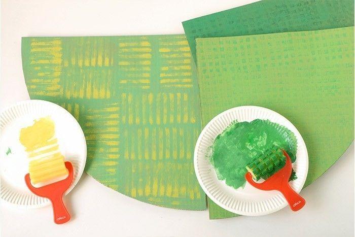 ETAPE 3/17 Pour créer le champ labouré, appliquer le rouleau en mousse à rayures enduit de peinture jaune. Pour le sol de la forêt et des espaces verts, se servir du rouleau mousse à petits carrés pour donner de la texture en utilisant un vert à peine plus foncé que le fond existant.