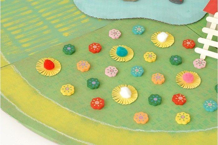 ETAPE 5/17 Le tapis de jeux en carton est prêt pour que les enfants s'amusent et se racontent plein d'histoires autour de la nature. Idée + : Pour personnaliser le lac, peindre des motifs de poissons rouges sur des galets.