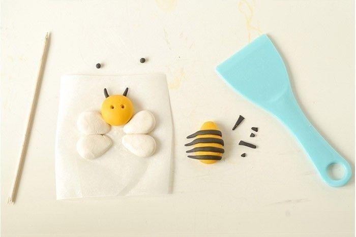 ETAPE 2/7 Placez les ailes sur un morceau de papier sulfurisé. Aplatir au centre et placer le tête. Fixer les antennes avec un peu d'eau, sous la tête. Percez 2 trous pour les yeux. Placez les rayures sur le corps et les aplatir pour fixer. Coupez les rayures qui dépassent.