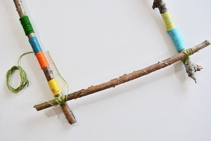 ETAPE 3/10 Assembler les 4 branches pour former le cadre du métier à tisser et les fixer entre elles par des fils enroulés sur plusieurs tours aux 4 croisements des branches. Conseil : Couper une longueur d'environ 1m de fil et le plier en deux, le nouer à une branche et enrouler d'un côté avec une extrémité et de l'autre avec l'autre extrémité de façon à se que les 2 fils se rejoignent à la fin et que le triple nœud final soit facilité.