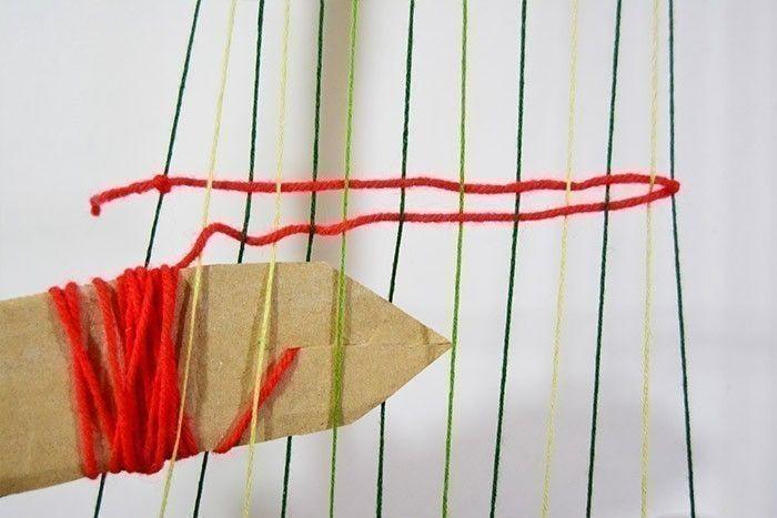 ETAPE 5/10 Couper un rectangle dans un carton et le couper en forme de flèche, l'entailler à l'horizontale et y enrouler une longueur de laine (1 à 2 mètres selon la hauteur de tissage souhaitée) en coinçant l'extrémité dans l'entaille. Nouer l'autre extrémité sur le 1er fil du métier à tisser puis commencer à tisser en passant la flèche sous tous les fils clairs pour le premier rang puis passer la flèche dans l'autre sens pour le 2ème rang mais cette fois sous tous les fils foncés. Continuer de cette façon le tissage sur la longueur souhaitée. Terminer par un double-nœud.