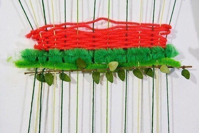 ETAPE 6/10 Poursuivre le tissage avec des fils chenille coupés selon la largeur du métier à tisser et insérés dessus-dessous. Insérer des branchages en coinçant sous quelques fils les extrémités pour les maintenir sans les abîmer.