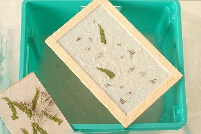 ETAPE 5/8 Remuez le mélange, plongez le tamis en l'inclinant dans le bac, le placer à l'horizontale et remonter doucement avec les deux mains, pour que la pulpe de papier se dépose sur le tamis de façon égale. Laisser égoutter le tamis sur le bac, toujours à l'horizontale. Astuce : à cette étape, on peut ajouter des feuilles séchées ou des pétales pour un autre effet de papier.