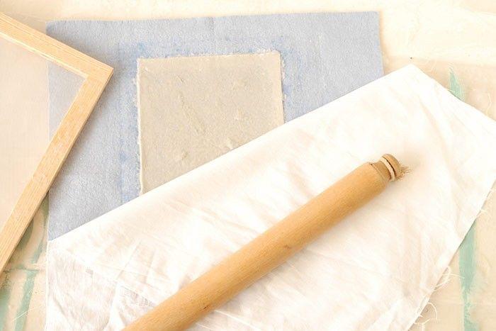 ETAPE 7/8 Poser un tissu sans pli ou torchon sur la feuille obtenue. Lisser avec la main. Essorer la feuille en passant plusieurs fois un rouleau à pâtisserie. La feuille va épouser les fibres du tissu choisi. Suspendre l'ensemble sur un étendoir avec des pinces à linge. Laisser sécher une nuit. Recommencez les étapes précédentes pour créer d'autres feuilles de papier tout en rajoutant la préparation dans le bac d'eau à chaque fois.