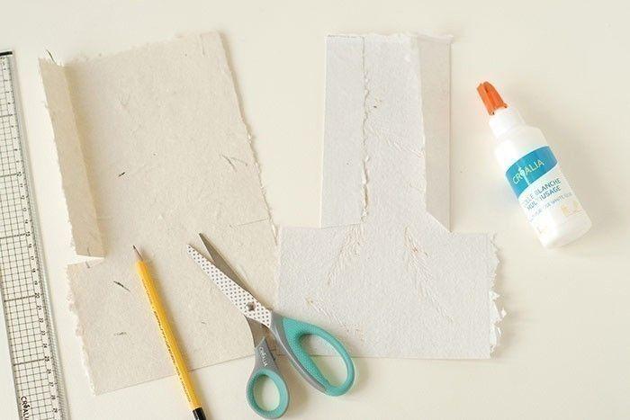 ETAPE 1/6 Placer votre feuille de papier recyclé à la verticale. Egaliser le bas de la feuille avec les ciseaux. Marquer un repère à 10 cm du bas de la feuille sur toute la largeur. Marquer un repère à 3 cm à droite et à gauche sur votre repère. Couper deux fentes en suivant vos repères. Rabattre et plier vers le centre les côtés supérieurs. Coller les rabats au dos.