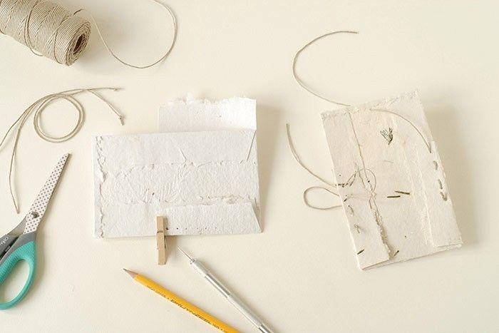 ETAPE 3/6 Sur le rabat de droite, tracer une ligne de repère à 0,5 cm du pli, marquer 8 repères au crayon à papier, espacées d'1 cm. Répéter l'opération sur le rabat de gauche dans l'autre sens. Pour créer le soufflet du vide-poche, pousser chaque pli des rabats contre le bord du vide-poche et maintenir l'avant et le dos de la pochette avec une pince à linge. Percer les trous au travers de toutes les épaisseurs de papiers. Couper 2 longueurs de 35 cm de ficelle. Faire un nœud à une extrémité. Passer l'autre extrémité dans les trous pour coudre les côtés.