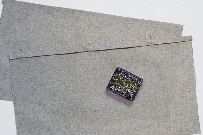 ETAPE 6/9 Coupez dans le tissu en lin deux rectangles de 25 x 42 cm. Sur chaque rectangle, faites un repli de 1 cm + 1 cm au fer à repasser, épinglez et surpiquez au point droit à 0,8 cm du bord. Surfilez* les trois autres côtés des rectangles au point zigzag.