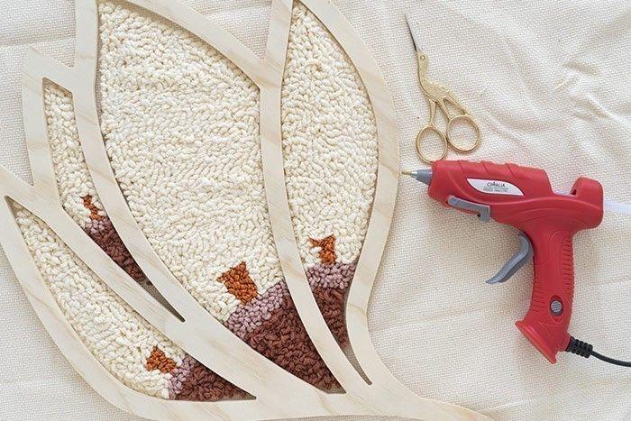 ETAPE 8/10 Positionnez la forme en bois sur vos motifs. A l'aide de la pointe des ciseaux faites ressortir les points. Puis avec le pistolet à colle de précision collez la toile sur la forme en la soulevant légèrement. Collez en partant de gauche à droite ou inversement