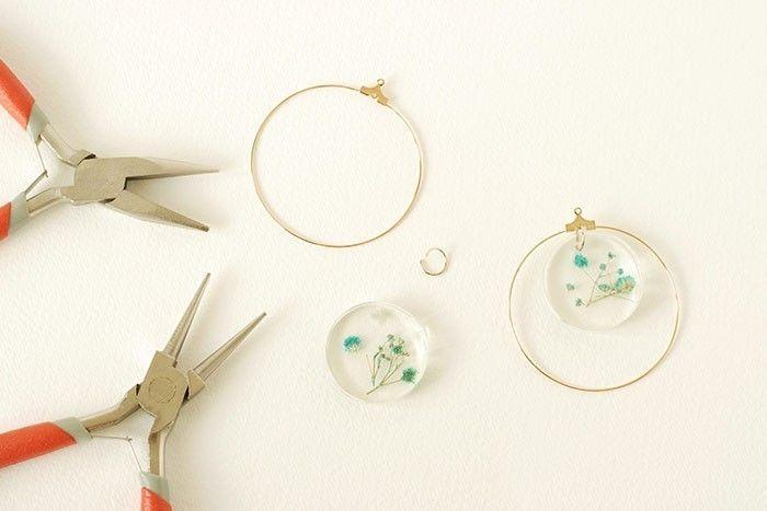 Etape 6/8 Monter les boucles d'oreilles. Ouvrir et écarter un anneau doré de 0,8 cm de diamètre et le passer dans l'ouverture du moulage. Le fixer au trou intérieur du pendentif rond « créole ». Refermer l'anneau avec des pinces plates et rondes. Insérer l'anneau sur la seconde résine.