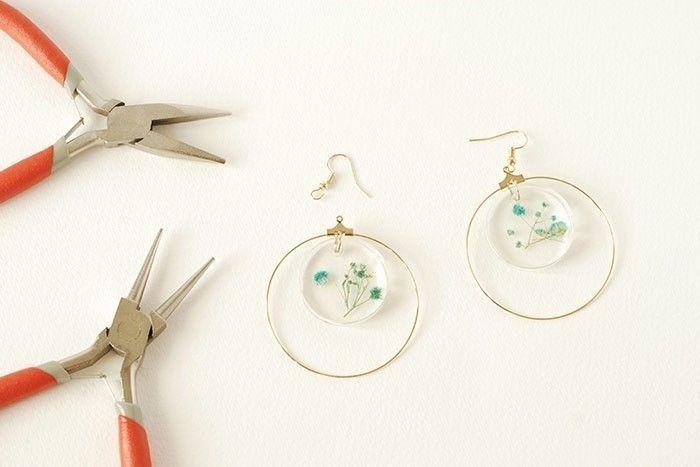 Etape 7/8 Prendre l'attache de la boucle d'oreille crochet. L'ouvrir au niveau du petit anneau en écartant avec les pinces à bijoux. Y glisser le pendentif créole avec la résine. Refermer l'anneau avec les pinces. Réaliser la seconde boucle d'oreille de la même façon.