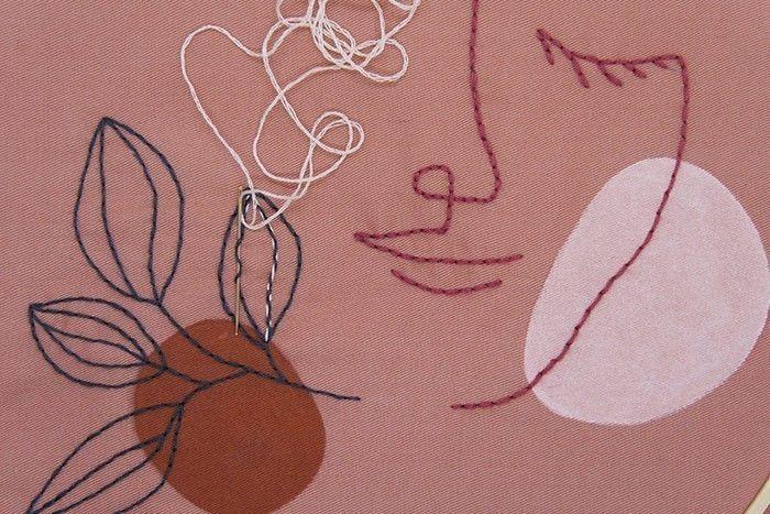 Etape 6/9 Finalisez la broderie sur les nervures des feuilles au point arrière surjeté : avec le fil rose pâle réaliser un zigzag avec le fil en glissant l'aiguille dans les points déjà réalisés.