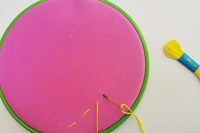 ETAPE 6/11 Retourner le tambour pour qu'il soit face à soi. Le fil sort du premier trou, l'enfiler dans le 2ème trou avec l'aiguille, il passe alors au dos du tambour. Au dos, passer à nouveau le fil dans le 3ème trou, il se retrouve à nouveau sur la face avant puis le passer dans le 4ème trou… etc jusqu'à broder tout le contour du cœur. Les points de broderie que vous venez de réaliser s'appellent des « points avant ».