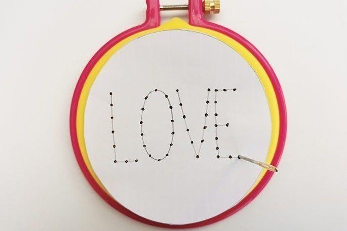ETAPE 9/11 Découper le rond « LOVE » du gabarit et le positionner sur le petit tambour. Piquer chaque point du mot LOVE avec l'aiguille au travers du gabarit.