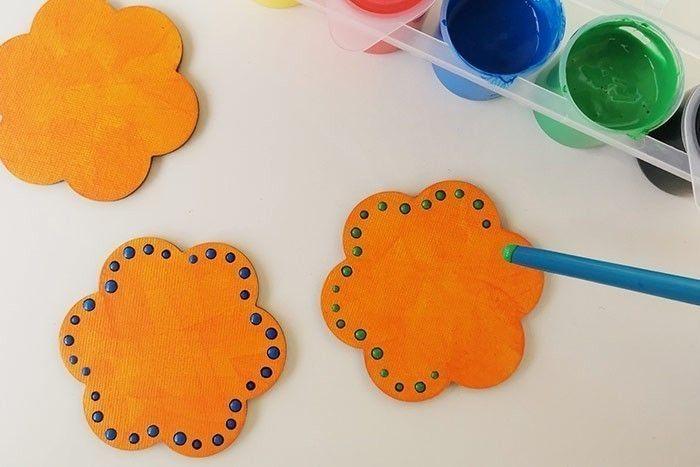 ETAPE 2/7 Tremper l'embout du manche de pinceau dans la peinture verte ou bleue et l'utiliser pour créer des points de peinture sur tout le contour des fleurs. Laisser sécher. Conseil : Vous pouvez mélanger du jaune et un peu de bleu pour obtenir la couleur verte si vous ne l'avez pas dans vos peintures..