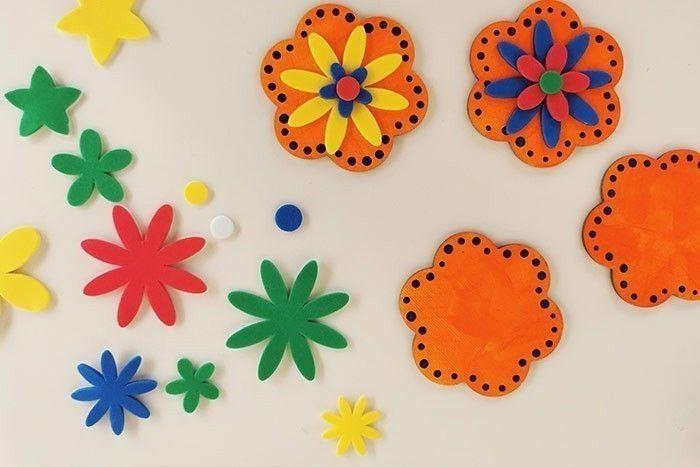 ETAPE 3/7 Décorer les mini toiles avec les stickers fleurs en mousse : une grande, une moyenne, une petite et un petit rond pour le cœur de la fleur. Varier les couleurs.