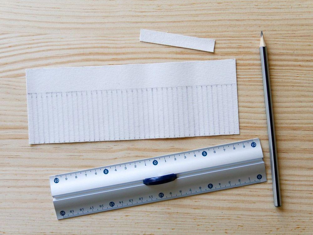 2.Tracez les repères sur le morceau de simili-cuir : ici, une bande de 1,2 cm x 7,5 cm qui formera l'anneau de fixation, puis un rectangle de 7,5 cm x 20 cm. Sur ce grand rectangle, repérez une bande de 2,5 cm de hauteur qui servira à rouler le pompon, puis sur le reste, tracez les repères des franges tous les 0,5 cm.