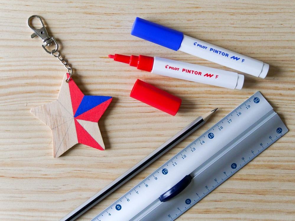 1.Avec une règle et un crayon à papier, tracez les lignes qui divisent l'étoile en partant du creux entre deux branches vers la pointe de la branche opposée. Alternez deux couleurs de feutres pour colorier chaque zone, l'une après l'autre. Vous pouvez poursuivre le motif sur la tranche de l'étoile et peindre le verso à l'identique (ou dans une seule couleur si vous préférez).