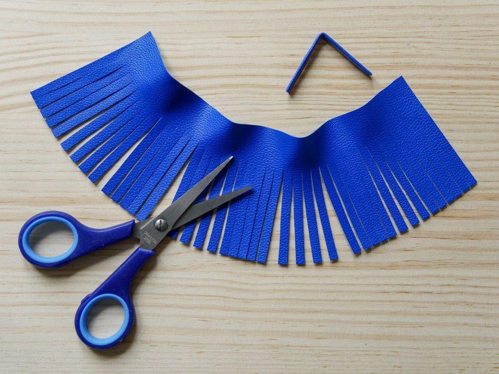 3.Avec des ciseaux précis, frangez le simili-cuir en suivant les repères. Pour former l'anneau de fixation, repliez la petite bande de simili-cuir sur elle-même pour obtenir une tige de 0,6 x 7,5 cm. Fixez avec de la colle universelle et maintenez quelques secondes pour que la colle prenne.