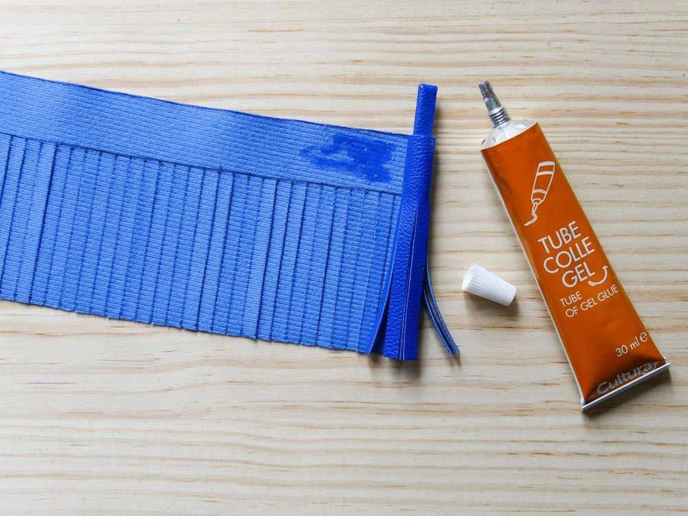 4.Repliez la tige sur elle-même en formant une boucle et placez-la à une extrémité du rectangle, au-dessus des franges. Fixez avec un point de colle, puis roulez le simili-cuir autour de la bride en encollant la partie non-frangée au fur et à mesure. Passez la bride dans l'anneau porte-clés et reliez le pompon à l'étoile en bois.
