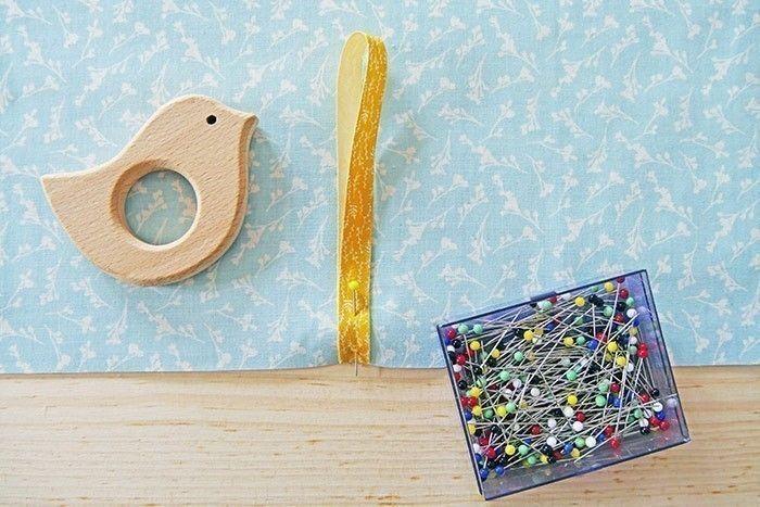Etape 2 Prenez le carré C et repérez le centre du bas. Sur l'endroit du tissu, épinglez une bride formée d'un morceau de 22 cm de ruban replié sur lui-même.
