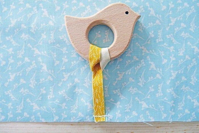 Etape 3 Fixez la bride au point droit, en réalisant plusieurs aller-retours pour renforcer. Glissez la bride dans l'anneau et refaites passer la boucle autour de l'anneau (vous pourrez ainsi ôter l'anneau pour le lavage du tapis ou pour le donner à l'enfant indépendamment du tapis).