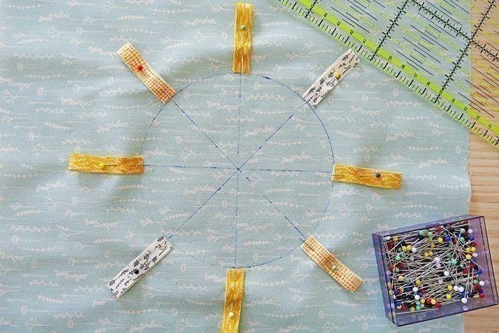 Etape 4  Prenez le carré I et repérez le centre du carré. Avec un compas et un feutre effaçable, tracez un cercle de 12 cm de diamètre. Tracez les 4 lignes passant par le centre du cercle, comme sur la photo. Epinglez 8 morceaux de rubans assortis de 8 cm, repliés sur eux-mêmes, chacun à l'extrémité d'une ligne.