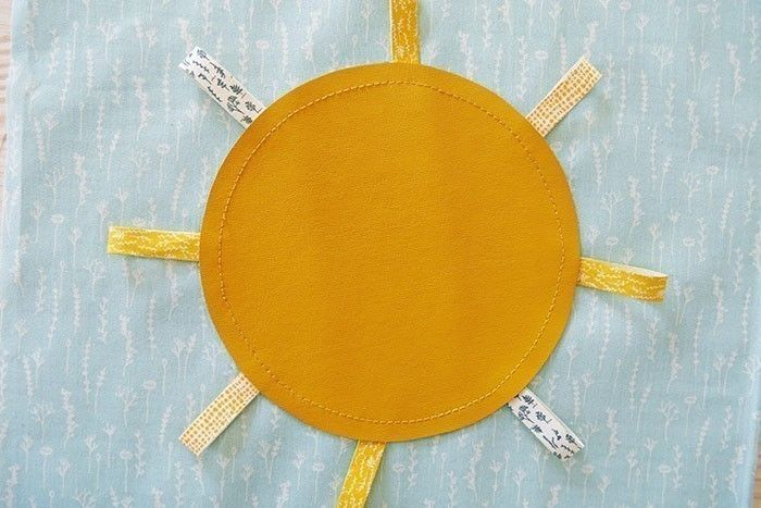 Etape 5 Recouvrez les rubans d'un disque de simili cuir de 14,5 cm de diamètre. Surpiquez au point droit, à 0,5 cm tout autour du disque. Effacez les lignes de repères (à l'eau ou à la chaleur selon le stylo que vous utilisez).