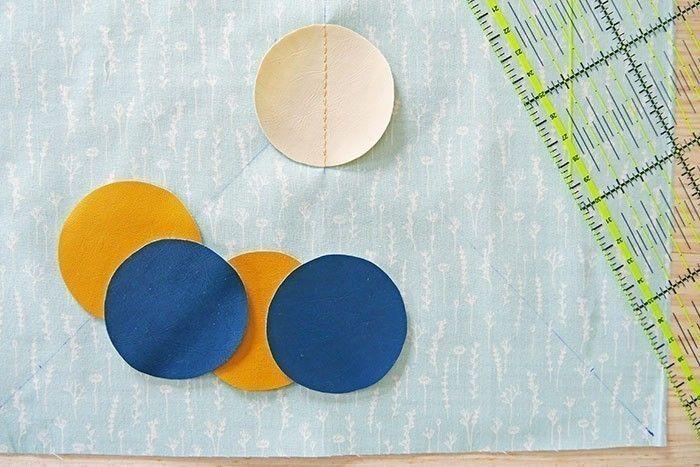 Etape 6  Prenez le carré A et tracez les deux diagonales au stylo effaçable. Coupez 5 pastilles assorties de 5 cm de diamètre dans le simili cuir. Placez la première pastille au centre du carré et surpiquez au point droit en formant une ligne médiane.