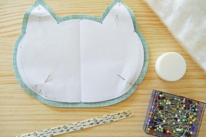 Etape 8 Téléchargez, imprimez et découpez le gabarit « tête de chat », coupez la forme dans deux épaisseurs de tissu en ajoutant une marge de 0,5 cm. Epinglez les deux formes bord à bord, endroit contre endroit. Glissez un morceau de ruban de 15 cm entre les deux épaisseurs, en positionnant l'une de ses extrémités au centre du bas de la forme, en dépassant à peine.
