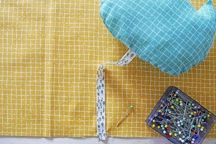 Etape 9 Piquez tout autour en laissant une ouverture de 5 cm. Crantez les marges de couture tous les 0,5 cm et retournez. Rembourrez avec des morceaux de molleton, glissez l'accessoire de bruitage « hochet » à l'intérieur et refermez l'ouverture en cousant à la main de petits points invisibles. Epinglez et cousez le ruban au milieu-bas du carré G, sur l'envers du tissu, en faisant plusieurs aller-retours. 