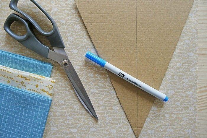 Etape 1/9 - Réalisez un gabarit dans un morceau de carton de récupération : tracez une ligne de 20 cm. A partir du milieu de cette base, tracez une ligne de 23 cm et réunissez les extrémités pour former un triangle. A l'aide de ce gabarit, coupez 16 triangles identiques dans les différents tissus assortis (par exemple, comme ici, 4 triangles dans 4 tissus différents).