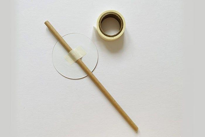 Etape 6 : Fixez une paille, bâtonnet en bois ou un cure-dent à l'arrière des cercles superposés à l'aide du ruban adhésif.