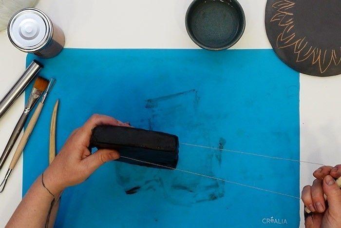 Etape 1 : Préparation de l'argile : coupez le pain de 1 kg en deux avec le fil à couper, et emballez la moitié dans du film alimentaire. Vous pourrez ainsi le conserver environ 2 semaines. Malaxez l'autre moitié pour la ramollir en humidifiant régulièrement vos mains. Formez une boule en tapant sur l'argile pour chasser l'air