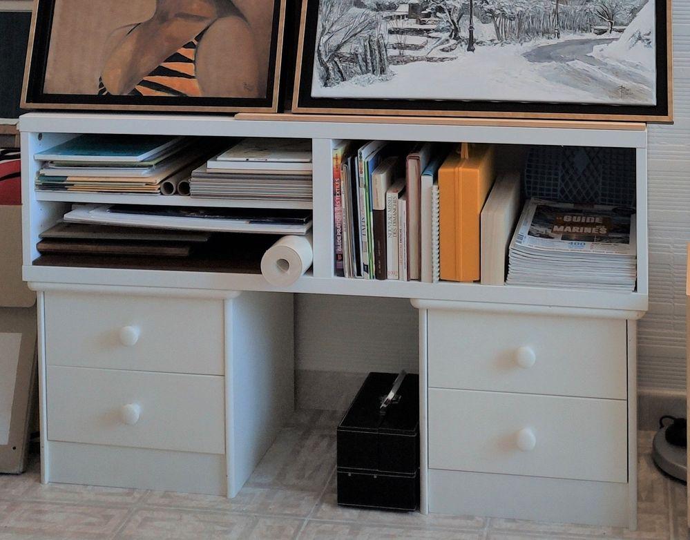 Le meuble TV posé sur les tables de nuit accuille les tableaux et tout le matériel de dessin!