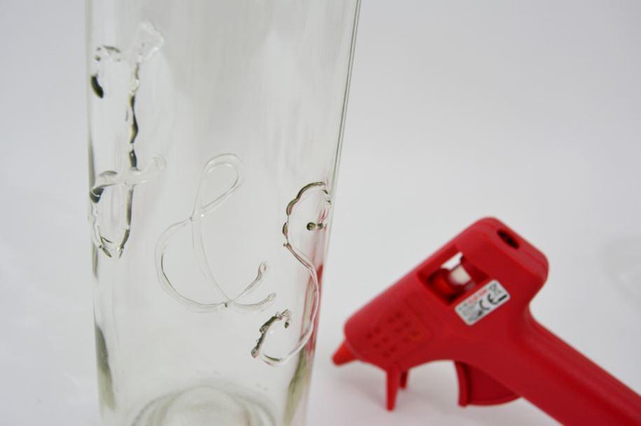 Les bouteilles : Ecrire les initiales des mariés avec le pistolet à colle sur la surface d'une première bouteille.