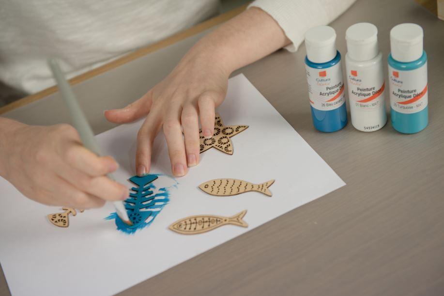 3. Peindre en coloris bleu sur une face les accessoires ajourés de la collection. Pour un rendu déco, utiliser différentes nuances de bleu. Laisser sécher. Coller les accessoires peints sur le fond des petits plateaux.