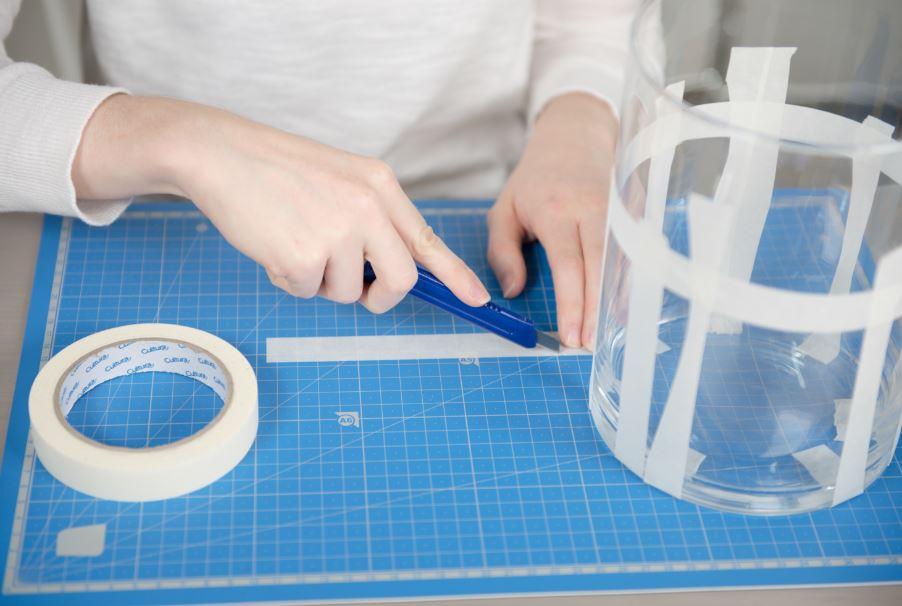4. À l'aide d'un cutter, couper le ruban de masquage dans sa largeur en bandes irrégulières. Positionner les bandes à intervalles irréguliers sur le contour du photophore. Placer une bande de ruban de masquage à la perpendiculaire.