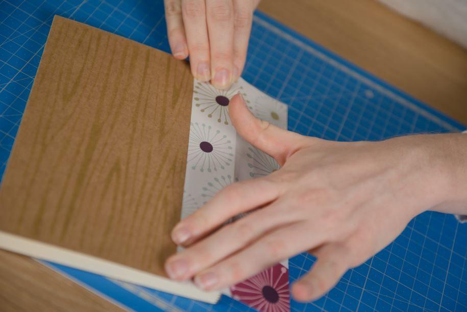2. Découper une large bande de papier de la collection et la coller sur la tranche du carnet.