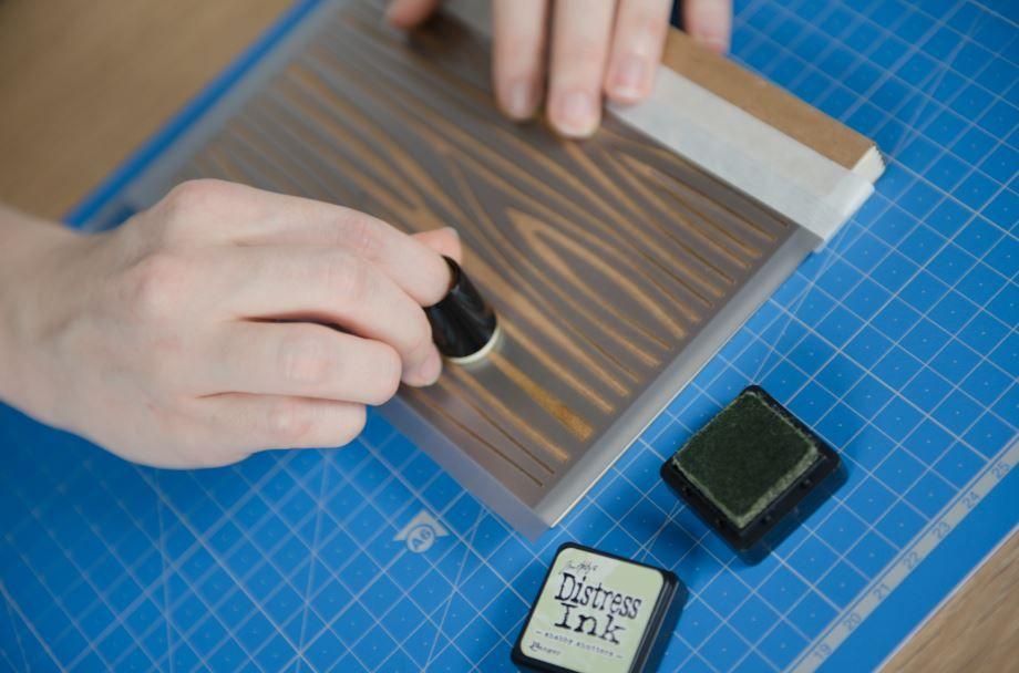 1. Fixer le pochoir « fond bois » sur la couverture du carnet à l'aide de ruban de masquage. Enduire l'éponge à doigt d'encre Distress et l'appliquer sur le pochoir. Retirer le pochoir et laisser sécher.