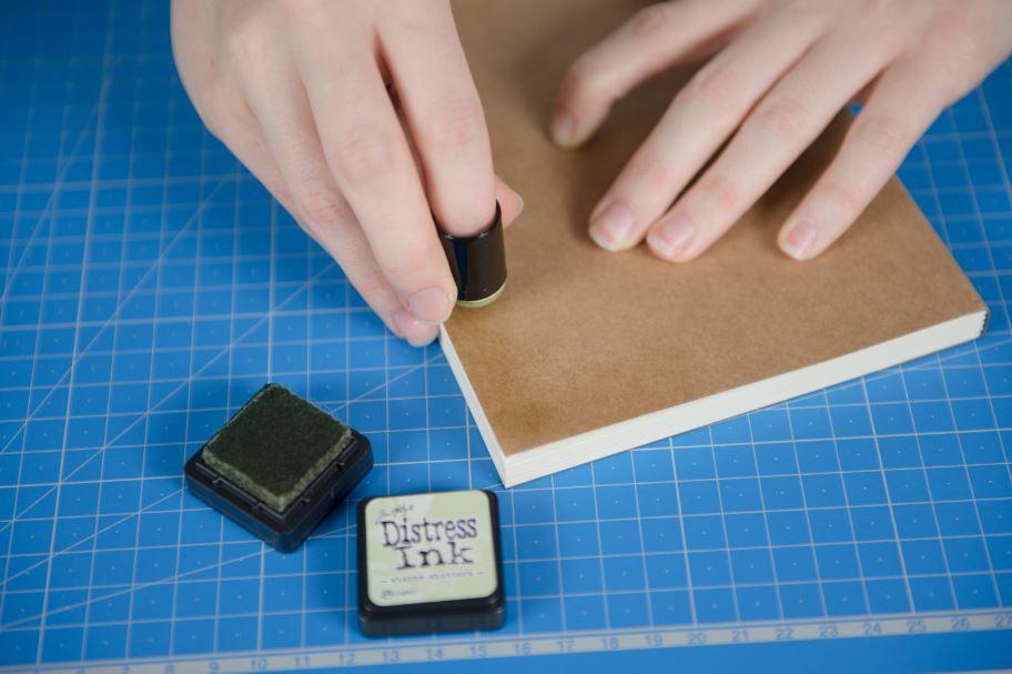 4. Enduire l'éponge à doigt d'encre Distress et appliquer l'encre en dégradé sur le contour de la couverture.