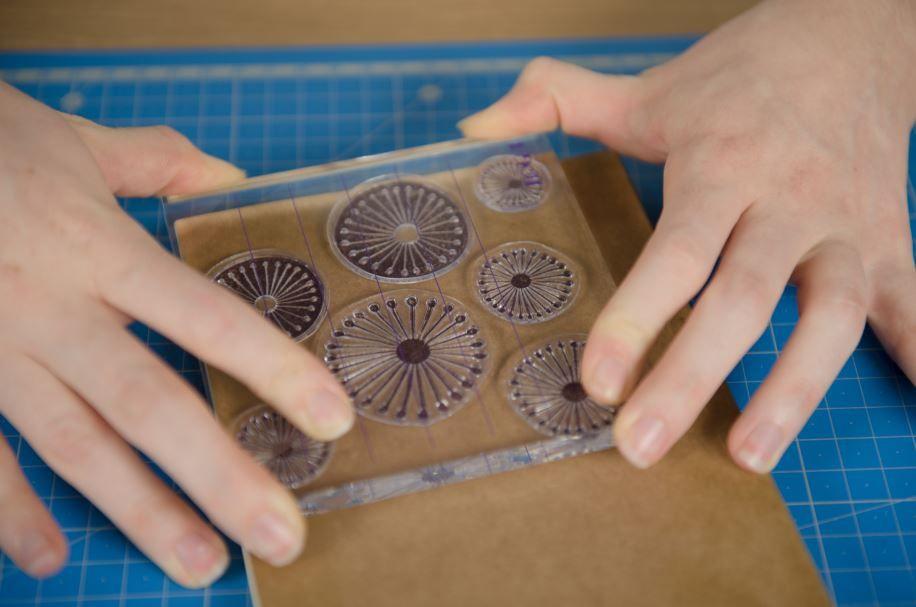 5. Positionner le tampon transparent « fleur » sur le bloc acrylique. Enduire le tampon d'encre Versafine et l'appliquer sur la couverture. Répéter cette étape pour recouvrir complètement la couverture du carnet.