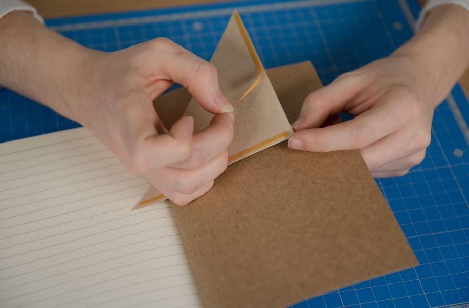 6. Découper un triangle avec un angle droit et deux côtés de 11 cm dans du papier kraft et superposer un second triangle de papier de la collection dont les dimensions seront réduites de 1 cm. Positionner deux bandes de double-face au verso du triangle de papier (sur les deux plus petits côtés). Coller le triangle sur la couverture intérieure du carnet.